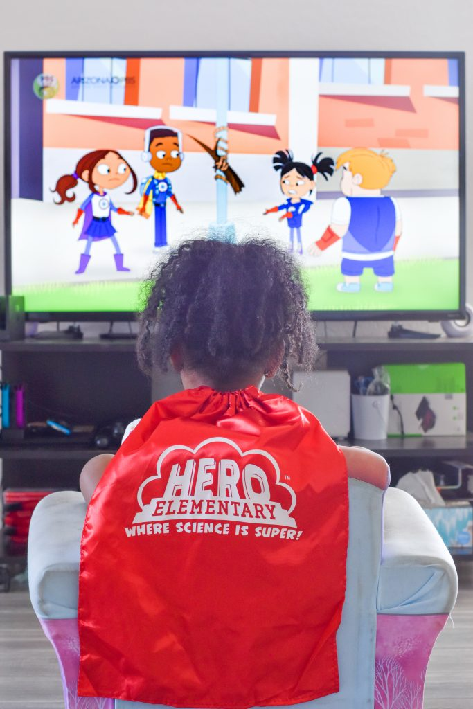 curly haired African American girl watching Hero Elementary with a red cape on that says Hero Elementary.